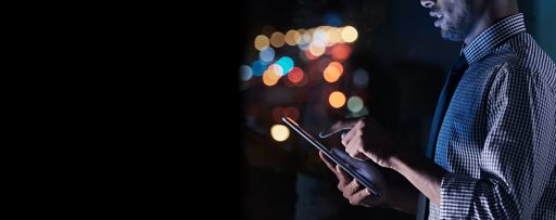 Shot of a young businessman using his digital tablet while working late