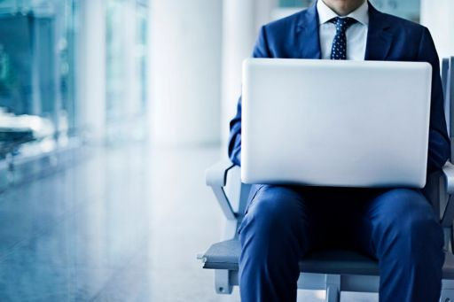 Businessman sitting down working, with laptop on knees