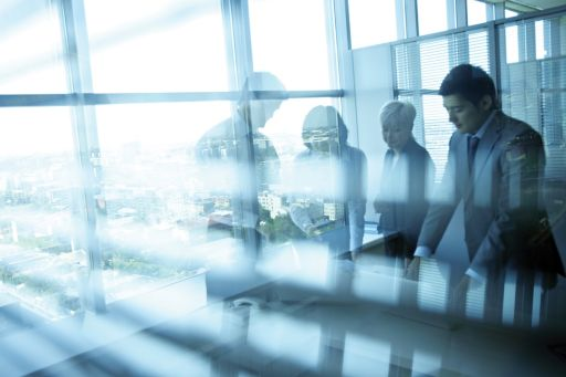 Businesspersons in a boardroom with shiny windows