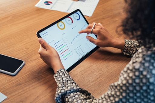 Businesswoman analyzing statistical business reports on her tablet