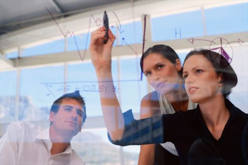 Businesswoman drawing graphs on glass wall