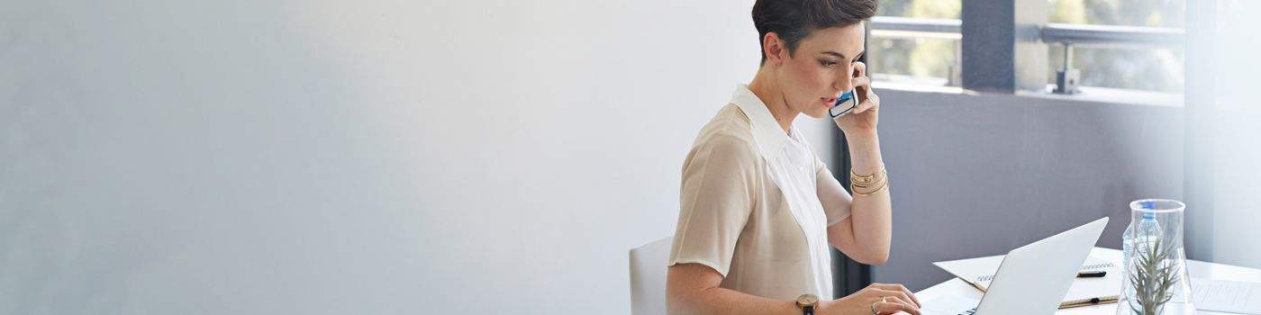 Businesswoman in office talks on the telephone