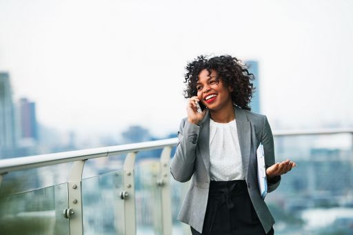Businesswoman standing on a terrace, making a phone call.