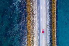 Car driving on road by ocean