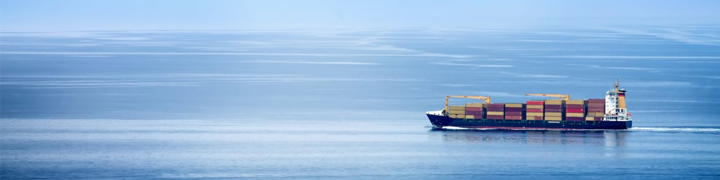 Cargo ship in sea with clear blue sky