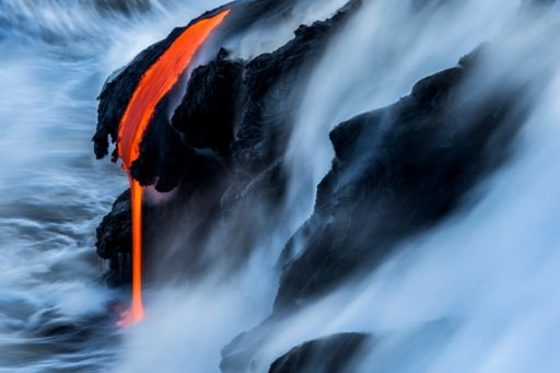 Changing state of distant lava flowing into wild ocean