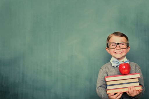 Local government: Best in class business cases - image of a school boy standing in front of a chalkboard holding books with an apple on top of them.