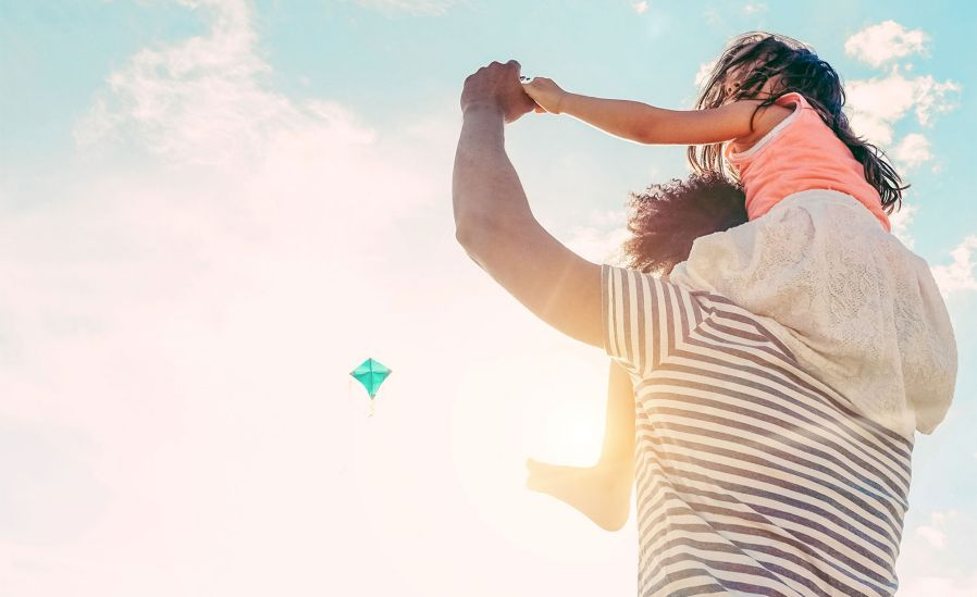 Child on father's shoulders in a bright sunny day