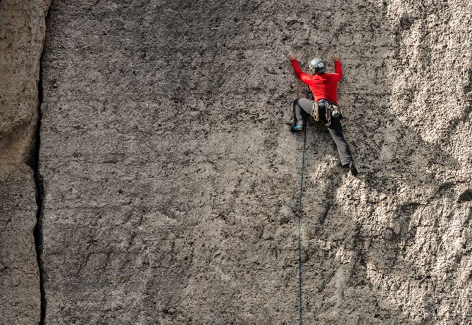 Rock climber wearing red outfit