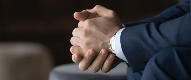 Close-up of businessman resting clasped hands on knees