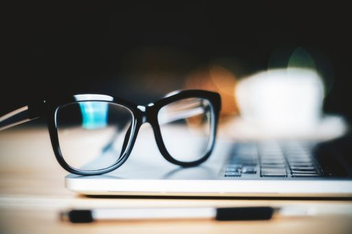 Close-up of glasses on laptop with pen