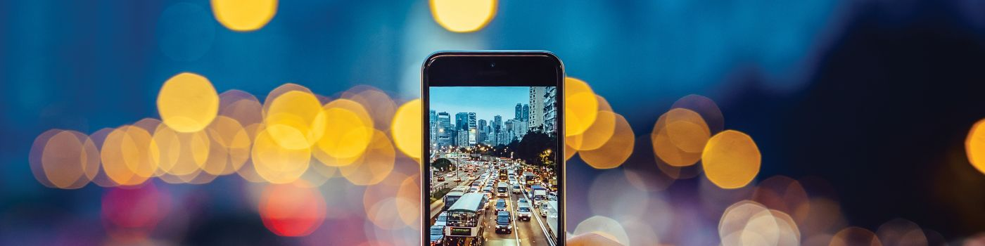 Woman capturing the busy traffic scene with smartphone