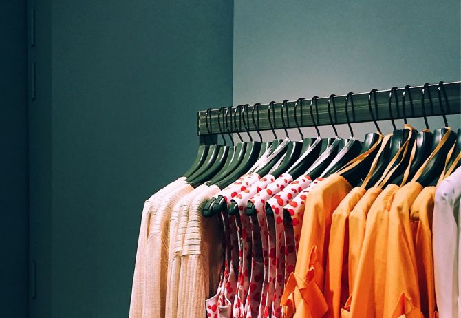 Colorful designer clothes hanging on a stand