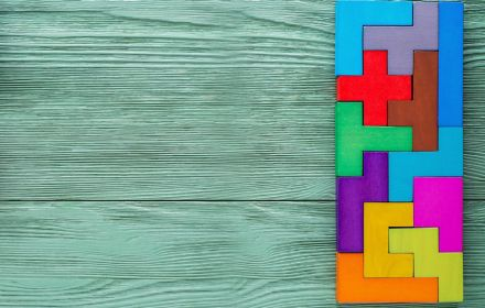 Colourful tetris blocks on a green wooden background