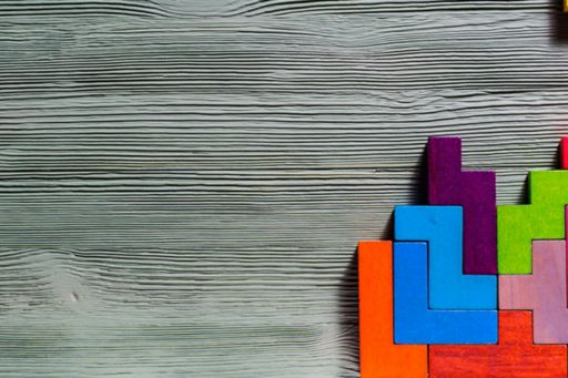Colourful wooden tetris blocks on a grey wooden background
