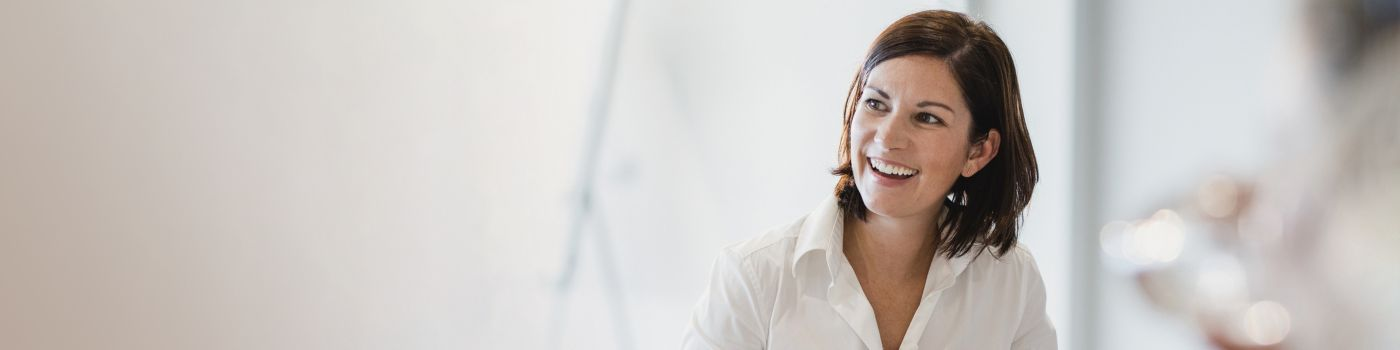 A smiling woman engages in friendly conversation during a meeting