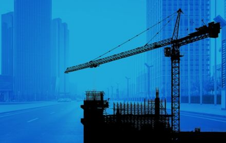 Construction crane with city skyline in background