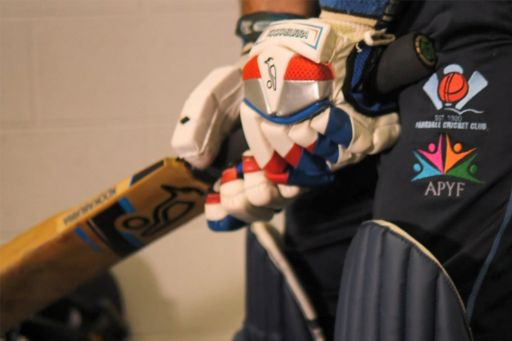 Cricketer wearing pads and gloves holding a cricket bat