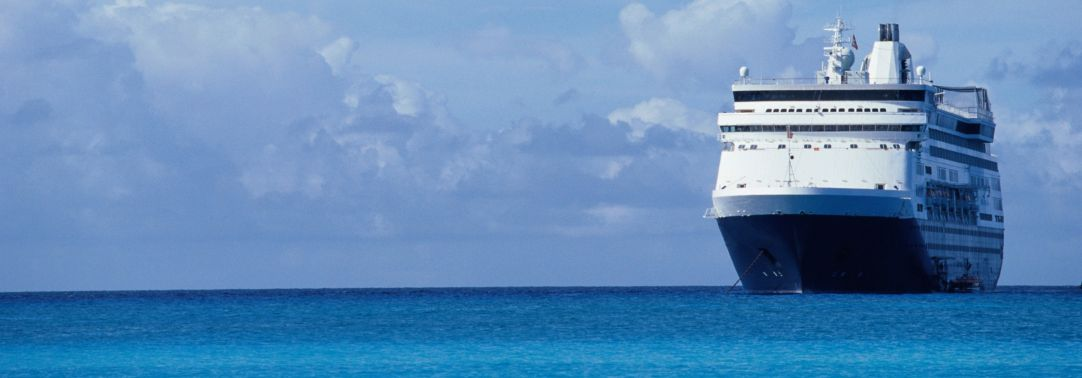 Cruise ship in sea against cloudy sky