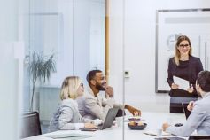 A smiling woman leads a customer success meeting