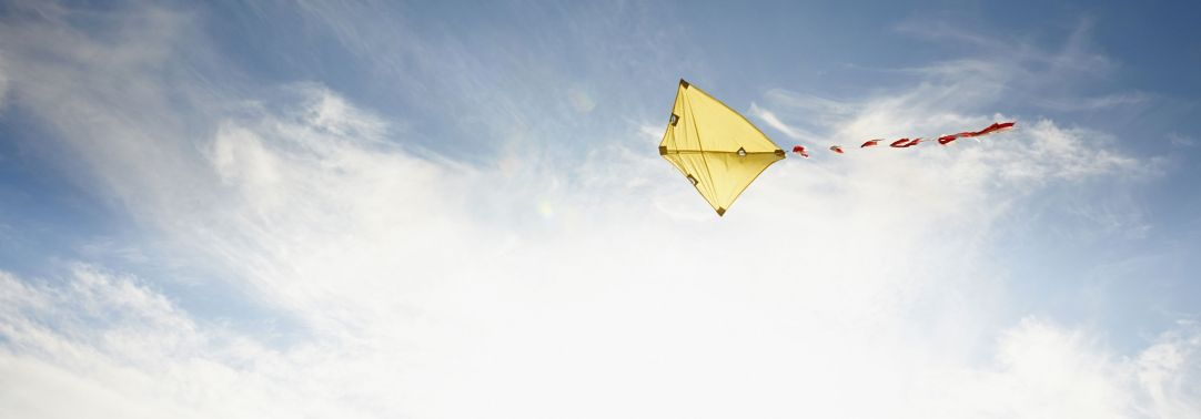 yellow kite flying in sky