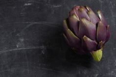 Picture of an artichoke on a marbled black background