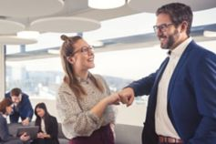 team colleagues smiling at each other and giving a fistbump