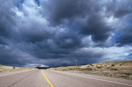Dark clouds above a deserted road