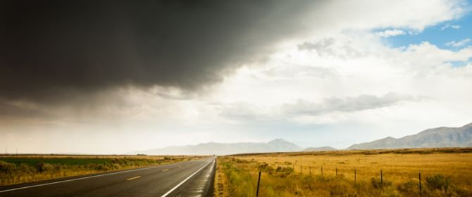 Dark clouds over an empty road