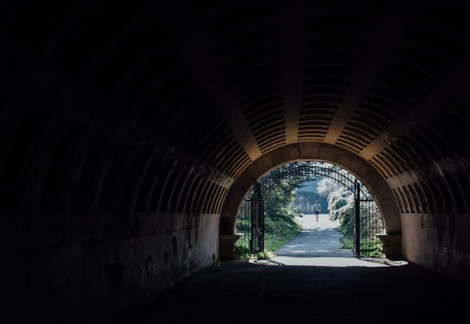 Dark tunnel leading to a park