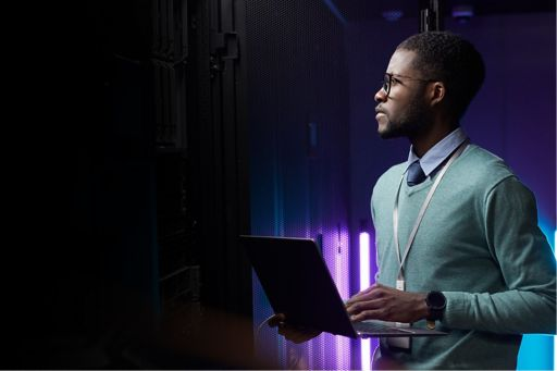 Data engineer holding laptop while working with supercomputer