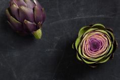 Split artichoke on a black, marbled surface