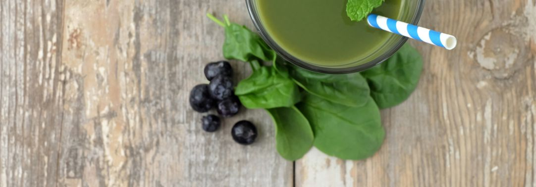 Detox drink in glass with leaves and berries on side