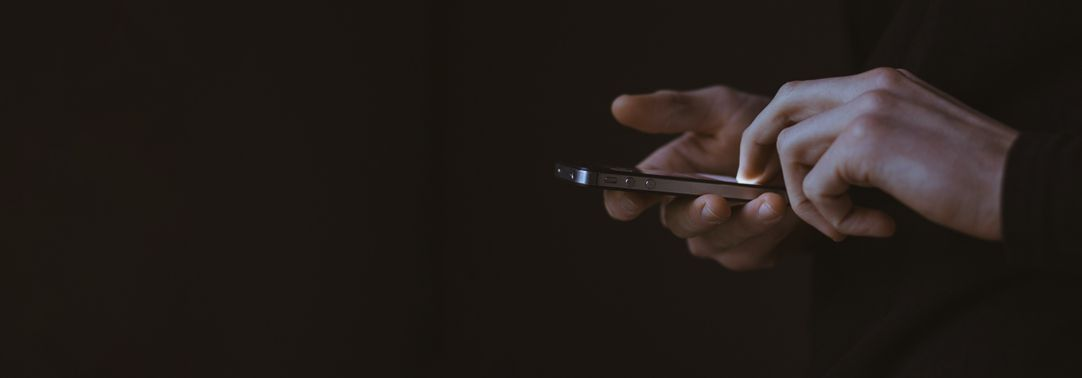 Hand holding phone on dark background