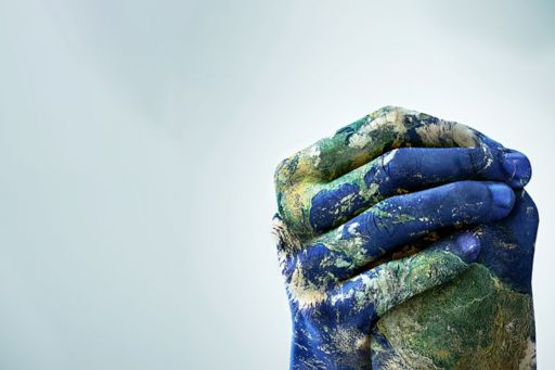 Planet Earth painted onto clasped hands