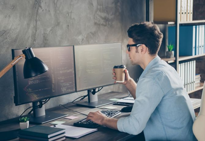 Employee testing computer while sitting at a desk holding a take-out mug in workplace
