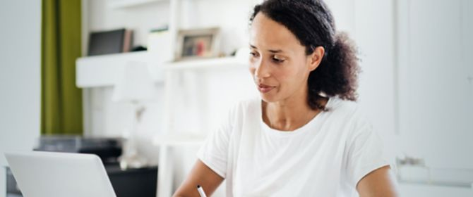 ATO compliance woman at kitchen table with laptop and pen