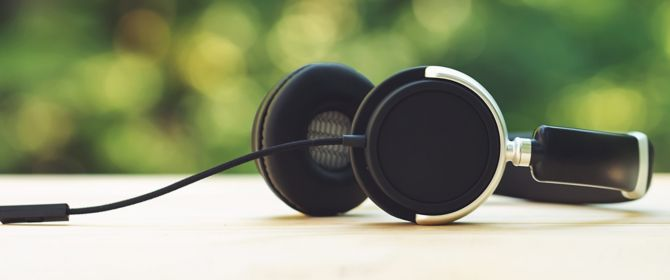 headphones sitting on a wooden table outside