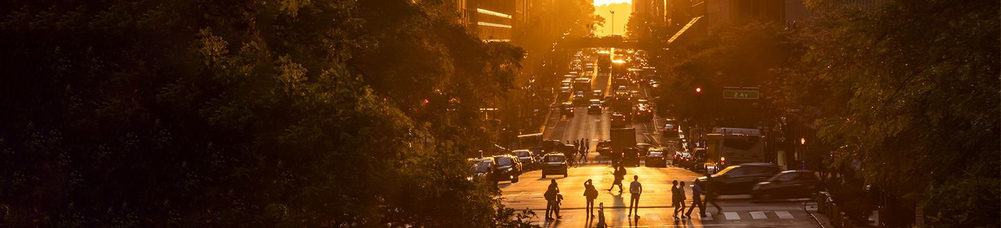 Rays of sunlight shining down on the people and traffic at the intersections along 42nd Street through Midtown Manhattan in New York City