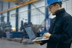 Factory worker in hard hat using a laptop