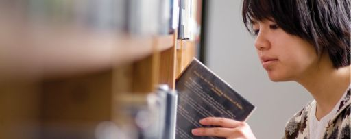 Female student placing a book on a library shelf