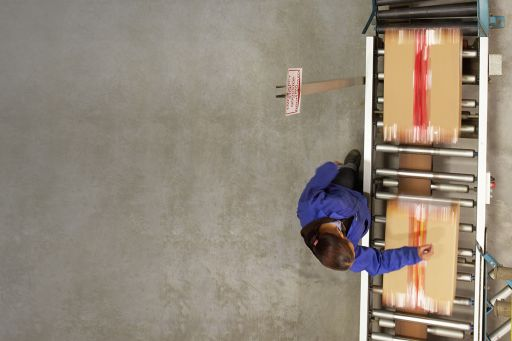Female worker working next to a conveyor belt managing boxes