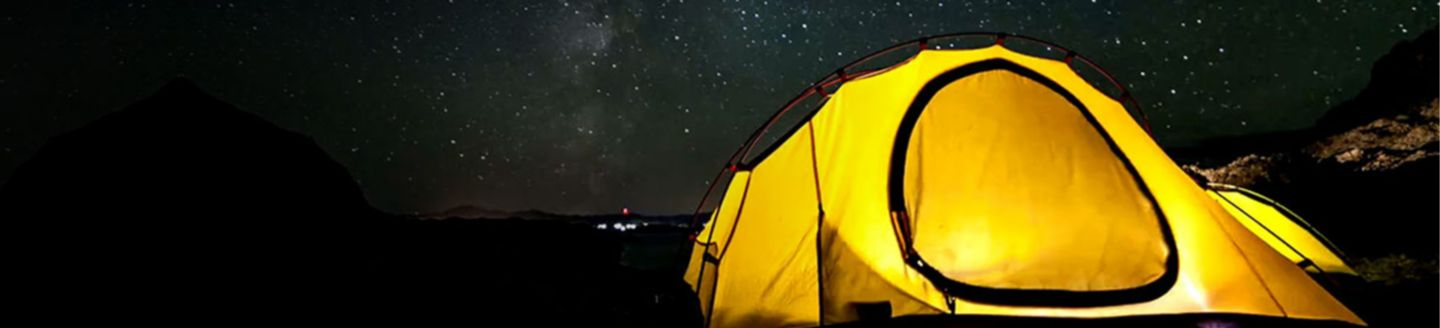 Yellow tent at night under a starry sky.
