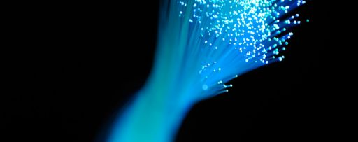 Bunch of light blue optic fibers against a black background.