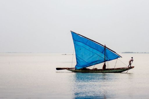 Fisher man on boat with blue sail in sea