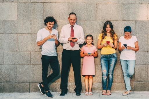 family-standing-against-wall-with-phones-in-hands