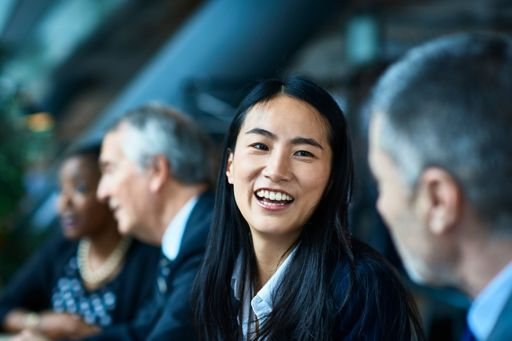 Focus on a girl laughing with the business people while sitting in a meeting