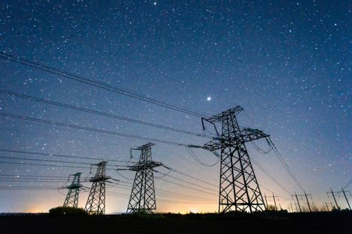 Four electric poles with night sky in background