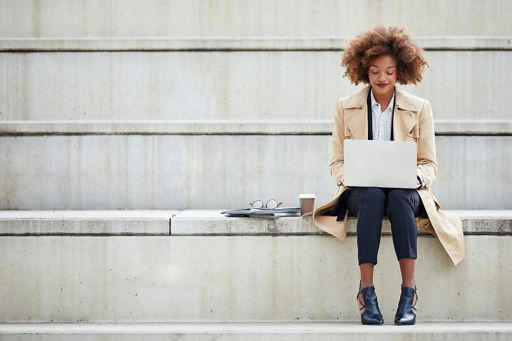 Woman sits on a staircase and has a laptop