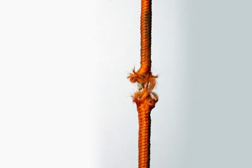 Frayed orange rope being pulled